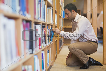 Handsome casual man cowering in front of bookshelves