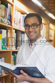 Intellectual handsome man posing holding an opened book in library