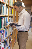 Handsome man reading concentrated a book standing in library