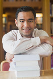 Attractive man posing in library leaning on a pile of books