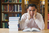 Handsome man sitting in front of an opened book in library
