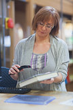 Mature female librarian scanning book