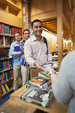 Attractive man handing a book to the female librarian