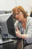 Irritated mature student working on computer