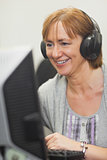 Happy mature woman working on computer