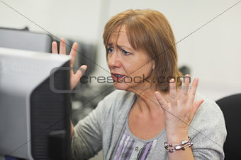 Annoyed mature woman working on computer