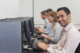 Cheerful mature student sitting in computer class