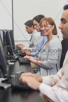 Female mature student sitting in computer class