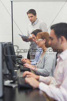 Teacher standing in front of computer class