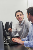 Two friendly men talking sitting in front of a computer