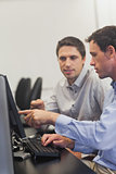Two mature men talking while sitting in front of computer