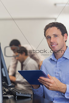 Content male student holding his tablet sitting in computer class