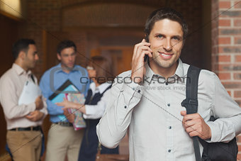 Cheerful attractive mature student phoning in corridor