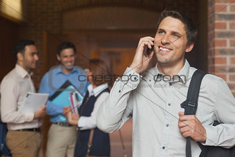 Happy mature student phoning with his smartphone