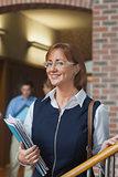 Happy female mature student posing in corridor
