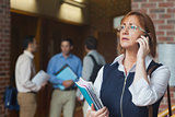 Female mature student phoning standing in corridor