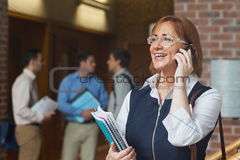 Amused mature student phoning standing in corridor