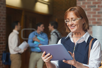Amused smiling mature woman using her tablet