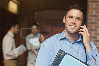 Attractive male mature student phoning with his smartphone