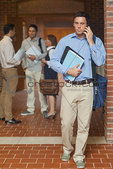 Attractive mature student phoning with his smartphone