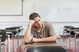 Tired male mature student sitting in class room