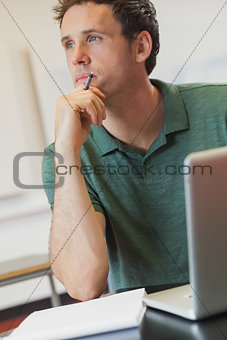 Attractive mature student sitting in classroom with his notebook