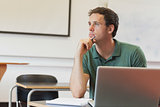Thoughtful handsome mature student sitting in classroom while learning