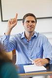Amused male mature student raising his hand
