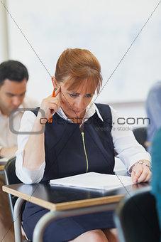 Focused mature student sitting in classroom