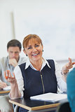 Amused female mature woman sitting in classroom