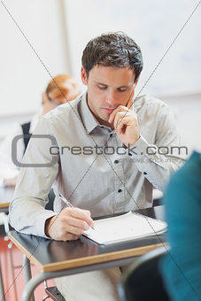 Focused handsome mature student sitting in classroom with classmates