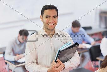 Portrait of handsome teacher posing in his classroom
