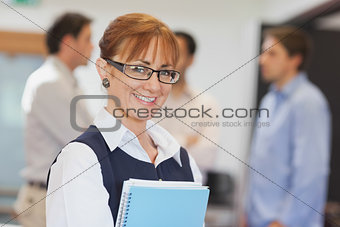 Portrait of female mature student posing in classroom holding some files