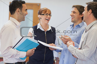 Group of mature students standing in classroom chatting