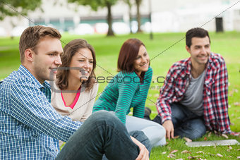 Casual happy students sitting on the grass laughing