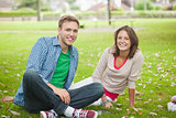 Casual smiling students sitting on the grass