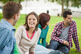 Casual laughing students sitting on the grass chatting