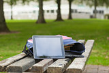 Purple schoolbag and tablet lying on park bench
