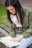 Content brunette student sitting on bench reading