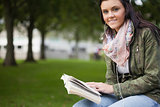 Gleeful brunette student sitting on bench reading