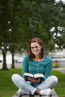 Smiling casual student sitting on bench reading