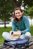 Cheerful casual student sitting on bench holding books