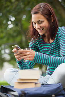 Cheerful casual student sitting on bench texting