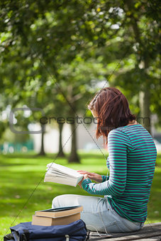 Casual student sitting on bench reading