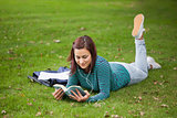 Content casual student lying on grass reading
