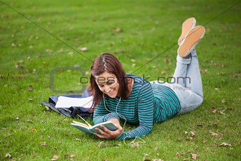 Happy casual student lying on grass reading