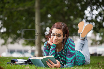Smiling casual student lying on grass reading