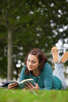 Attractive casual student lying on grass reading