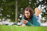 Attractive casual student lying on grass texting