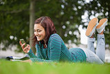 Smiling casual student lying on grass texting